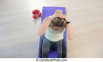 Slow motion video of young exhausted woman doing sit-ups on floor at living room. View from high point