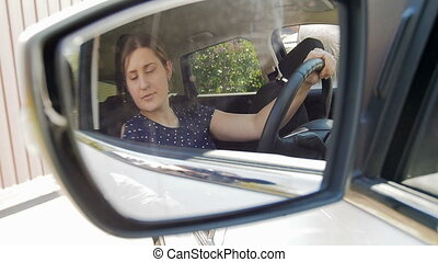 Slow motion video of young female driver adjusting side view...
