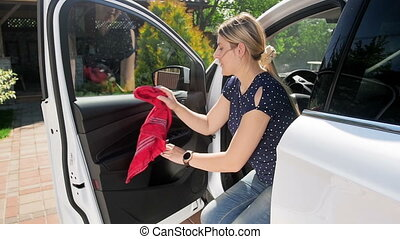 Slow motion video of young female driver cleaning her with red microfiber cloth