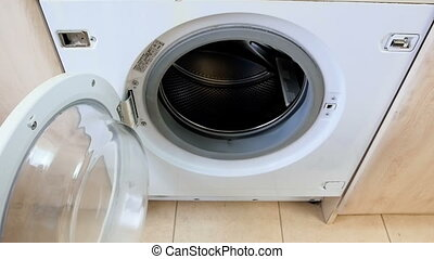 Slow motion video of young female hand throwing dirty clothes in washing machine at laundry