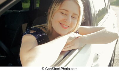 Slow motion video of young smiling woman sitting at car...