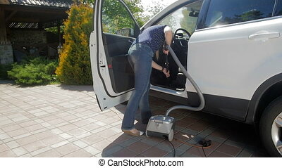 Slow motion video of young woman cleaning her car with vacuum cleaner at house backyard