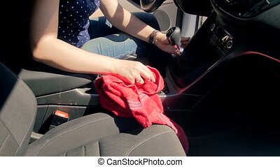 Slow motion video of young woman cleaning very dirt car salon with cloth
