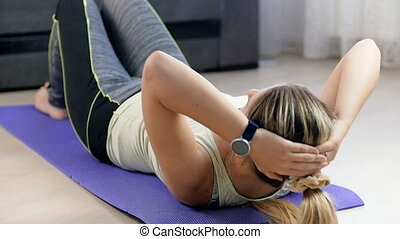 Slow motion video of young woman doing abs crunches on floor at living room