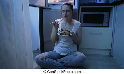 Slow motion video of young woman enjoying eating cake on kitchen at night