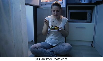 Slow motion video of young woman in pajamas eating cake at night. Concept of unhealthy nutrition and dieting