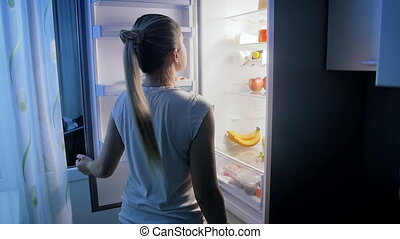 Slow motion video of young woman on diet looking inside of refrigerator at night