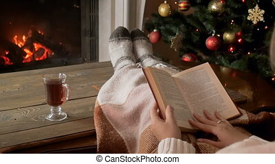 Slow motion video of young woman reading book on sofa next to burning fireplace and drinking tea on Christmas night