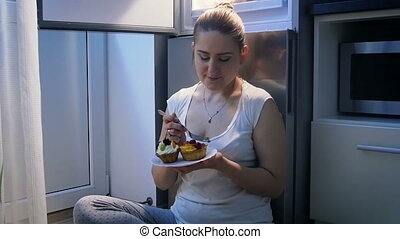 Slow motion video of young woman sitting on floor at kitchen and eating sweet cake