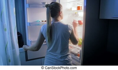 Slow motion video of young woman taking bottle of milk from refrigerator at night