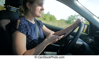 Slow motion video of young woman typing message on mobile phone while driving car is dangerous driving