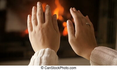 Slow motion video of young woman warming her hands at burning fireplace