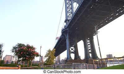 SLOW MOTION: View from under the Brooklyn Bridge in New York City USA on Sunny Day Green Grass with Sunlight