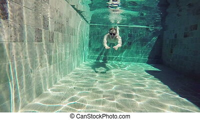 Slow motion ,View from water on the young sports man floating under water in the pool