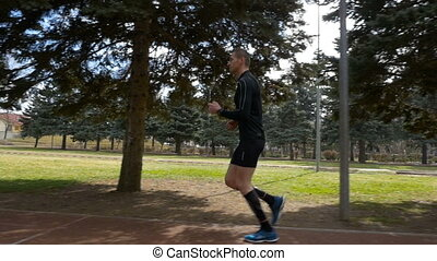 Slow motion view of a sportsman jogging in the park
