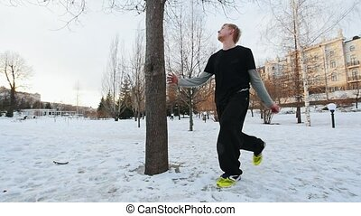 Slow motion view of acrobat athlete in winter park - work out parkour - a tracer blonde man jumps a backflip