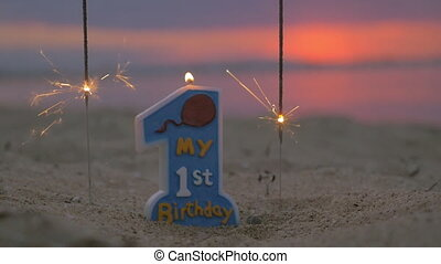 Slow motion view of candle and two sparklers standing in the sand on beach against blurred sunset