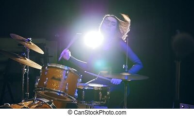 Slow-motion view of flowing black hair - young female plays drum rock at garage, slow-motion