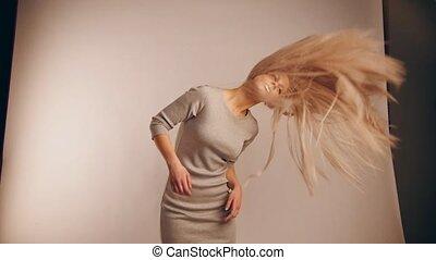 Slow-motion view of flowing hair in photo studio, caucasian girl model