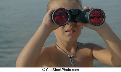 Slow motion view of small boy watching with binoculars against blurred sea