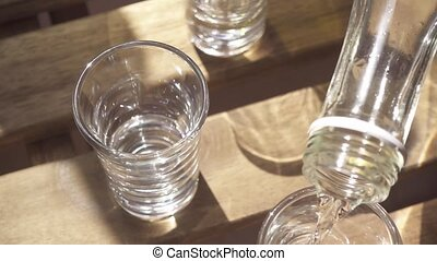 Slow motion vodka is poured into a glass from a bottle -...