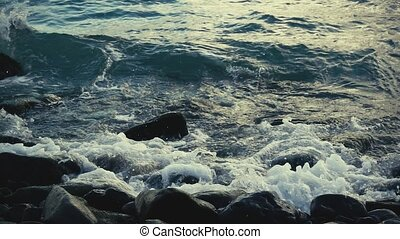 Slow motion waves break on rocks on the shore