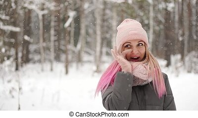 Slow motion, winter woman in the woods watching the snow...