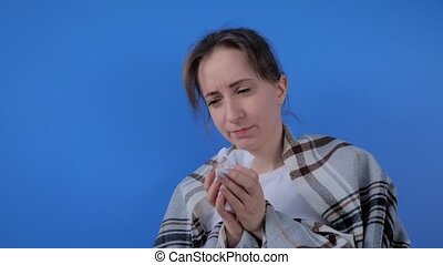 Slow motion: woman feeling sick, sneezing into facial tissue against blue wall