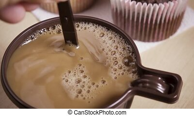 Slow motion woman stirs coffee with cream in a mug