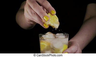 Slow motion. Women's hands squeeze a slice of lemon - Slow...