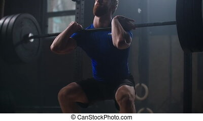 Slow motion: Young athletic man squats with barbell in gym. Man testing hes strength by holding a barbell with heavy weights on her shoulders as he squats