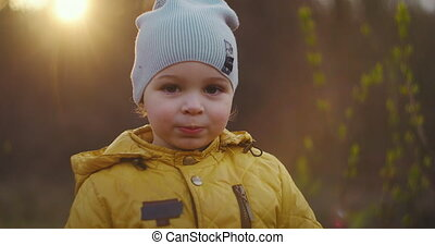 Slow motion: Young boy in a yellow jacket Explore the world around him while sitting in the forest in the sun. Enjoy and laugh in the woodland. Free cheerful childhood in the Park in nature.