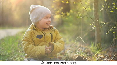 Slow motion: Young Boy in Yellow Jacket Explore the World Around Him While Sitting in the Forest in the Sun. Enjoy and laugh in the woodland. Free cheerful childhood.