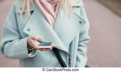 Slow motion young Caucasian lady using smartphone. Pretty 20s blonde with long blonde hair making video call. Tilt up.