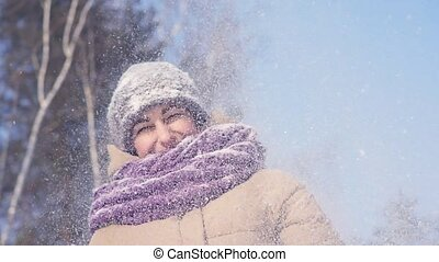 Young cheerful woman blowing on the snow in the palms