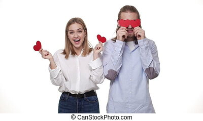 Slow-motion Young couple together playing paper hearts in casual smart cloths.