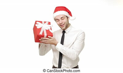Slow-motion young handsome businessman curiously listen inside the festive present.