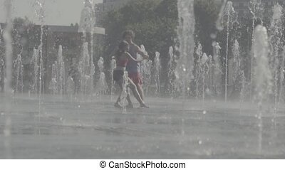 Young happy couple dancing in the fountain
