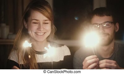 Slow motion. Young happy couple sitting at home in the evening and holding the sparklers, enjoying time together.
