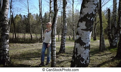 Slow motion ,Young is happy the woman with a long fair hair a white sweater and blue jeans goes on the birch wood
