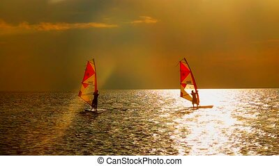 slow motion Young man practicing windsurfing on the waves in...