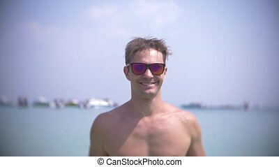 slow motion, young man stands in the sea with sunglasses splashes water and smiles