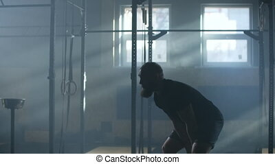 Slow Motion Young man swinging the two kettlebell in the ...