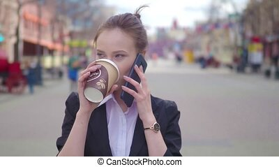 Slow Motion Young successful businesswoman using smart phone in city downtown, professional female employer talking with business partner drinking coffee. Business district skyscrapers in background