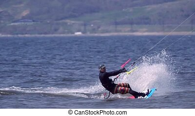SLOW MOTION:A kiteboarder of male jumps over the surface of...