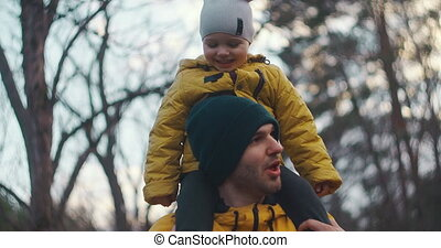 Slow motion:Happy family dad and son little boy fatherhood concept. Beautiful father with his baby son outdoor at park. Concept of happy family. Child sitting on his lifestyle father neck.