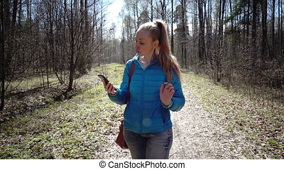 Slow motion,The young happy woman in a blue jacket and jeans lit with kontrovy light goes on a path of the park and speaks by phone