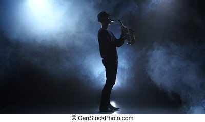 Slow motive on the saxophone. Musician in a smoky studio