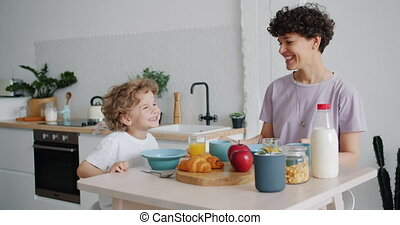 Slow moton of happy mother and son laughing at kitchen table...