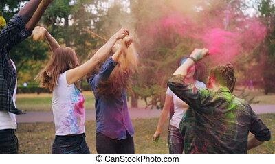 Slow moton of joyful men and women enjoying Holi colors...